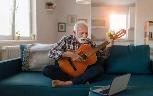 Happy good looking elderly man in a plaid shirt sits on a sofa in the living room and learns to play acoustic guitar online using a Laptop